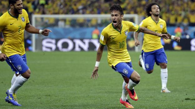 Drei brasilianische Fussballspieler jubeln auf dem Rasen im Stadion