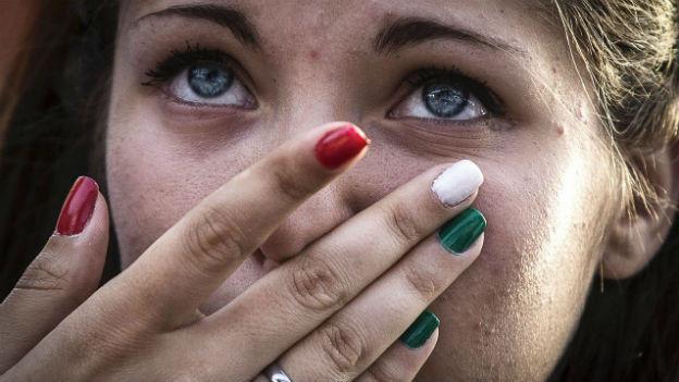 Grossaufnahme einer Frau mit Fingernägeln in den Farben der italienischen Flagge trauert mit Tränen in den Augen.