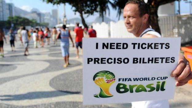 Ein Fussballfan sucht an der WM nach Tickets. Auf seinem Schild steht: I need tickets.