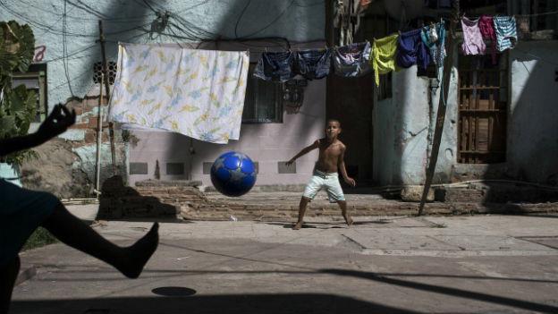 Zwei Jungen in Rio de Janeiro spielen auf der Strasse Fussball.