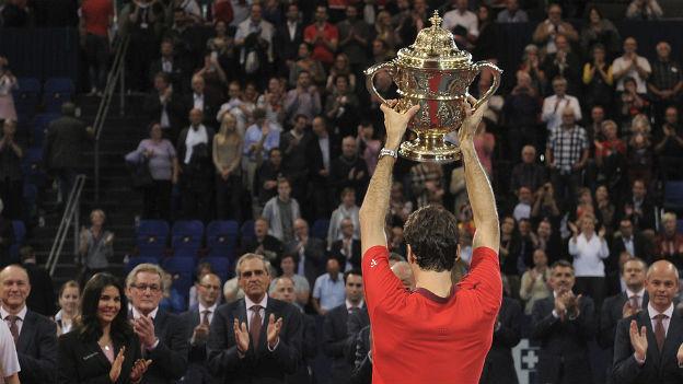 Roger Federer von hinten fotografiert, er stemmt den Siegerpokal der Swiss Indoors in die Höhe.