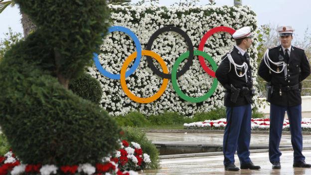 Zwei monegassische Polizisten in Uniform stehen vor einer Blumenwand, auf der die olympischen Ringe zu sehen sind.