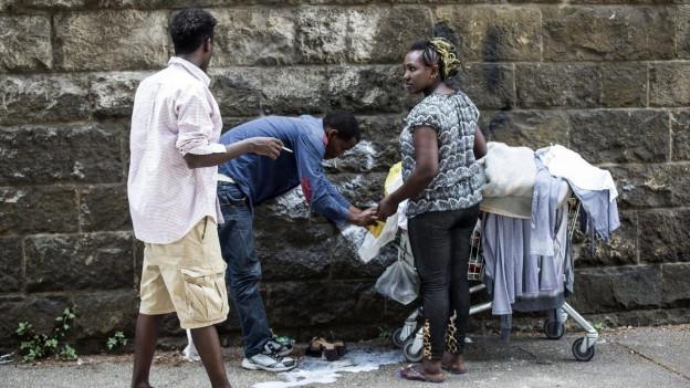 Flüchtlinge schieben ihre wenigen Habseligkeiten in einem Einkaufswagen durch die Strassen Roms.