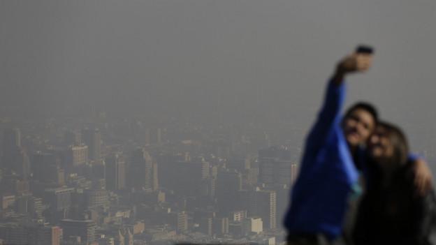 Zwei Touristen schiessen ein Selfie - im Hintergrund sieht man den Smog über der Stadt.