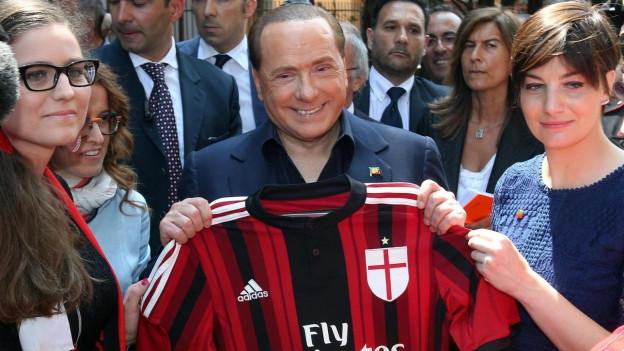 Silvio Berlusconi umringt von Fans mit einem rot-schwarzen Milan-Leibchen.