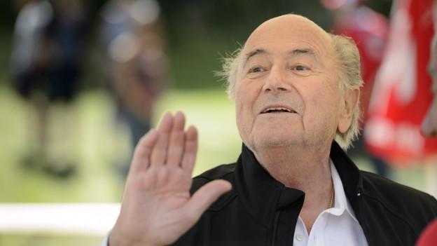 Grossaufnahme von Sepp Blatter, er scheint in die Ferne zu blicken und macht eine Art abwehrende Handbewegung.