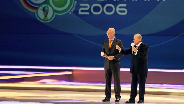 Beckenbauer, Blatter auf einer Bühne, dahinter Schriftzug Germany 2006.