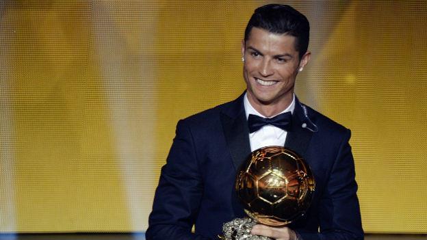 Fussballer Cristiano Ronaldo posiert lächelnd vor einer goldenen Wand und präsentiert seine Auszeichnung, einen goldenen Fussball.