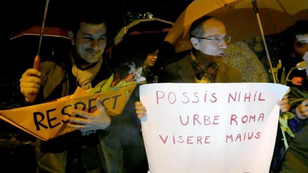 Zwei Männer mit Transparenten und Regenschirmen.