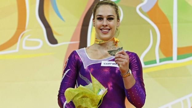 Das Bild zeigt die Kunstturnerin Giulia Steingruber in einem Violetten Dress, mit Goldmedaille und Blumenstrauss.