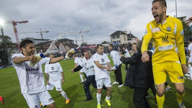 Spieler des FC Lugano jubeln vor Freude und spritzen sich gegenseitig mit den Trinkflaschen nass.