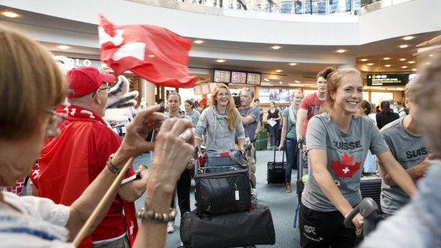 Ankunftshalle am Flughafen in Vancouver: In der Mitte lächelnde Spielerinnen, am Bildrand Menschen mit Fotokameras und Schweizerfahnen.
