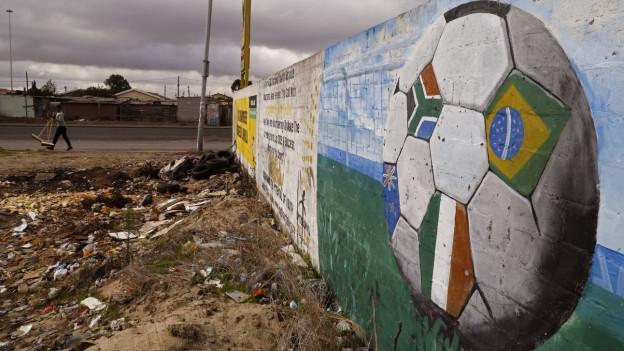 Eine Mauer mit einem aufgemalten Fussball und verschiedenen Landesflaggen in Khayelitsha.