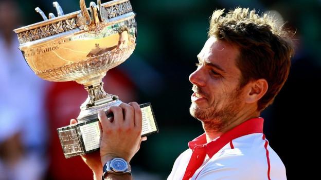 Stan Wawrinka stemmt den Siegerpokal der French Open in die Höhe und lächelt.