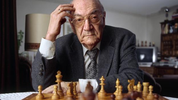 Viktor Kortschnoi sitzt hinter einem Schachbrett.