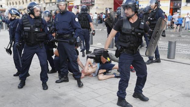 Eine Gruppe französischer Polizisten in Kampfanzügen umringt einen Mann, der zu Boden gedrückt wird
