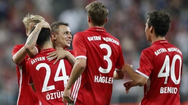 Spieler von Bayern München feiern auf dem Feld.