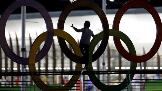 Ein Mann klettert auf die olympischen Ringe in der Nähe der Basketballhalle im Olympiapark.