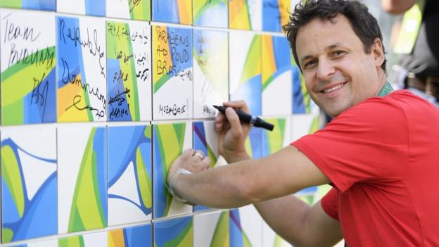 Ralph Stöckli, Leiter der Schweizer Delegation, unterzeichnet eine Wand während der Begrüßungszeremonie von Team Schweiz im Olympischen Mediendorf in Rio de Janeiro, Brasilien.