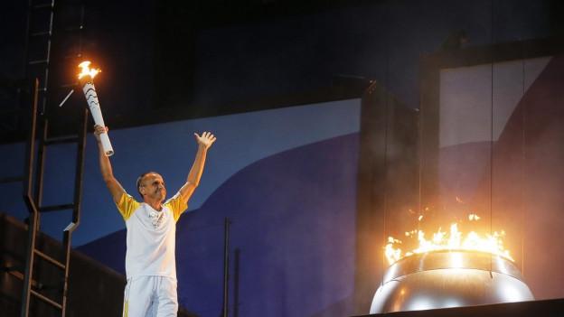 Sportler mit erhobenen Armen und Fackel neben dem olympischen Feuer.