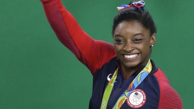 Simone Biles trägt eine Goldmedaille um den Hals.