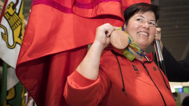 Die Schweizer Sportschützin Heidi Diethelm Gerber posiert mit ihrer Bronzemedaille bei ihrem Empfang am Flughafen.