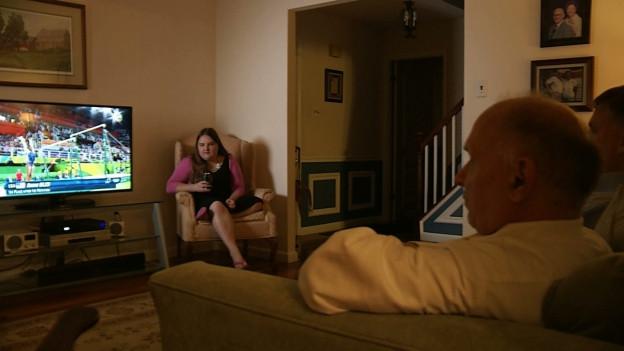 Menschen sitzen vor einem Fernseher. Es laufen die Olympischen Sommerspiele in Rio
