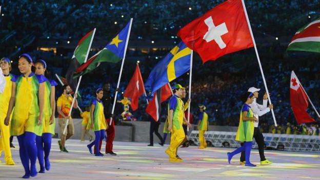 Goldmedaillen-Gewinner Nino Schurter trägt an der Abschlusszeremonie in Rio die Schweizer Fahne, rund um ihn herum sind Athleten aus anderen Nationen..