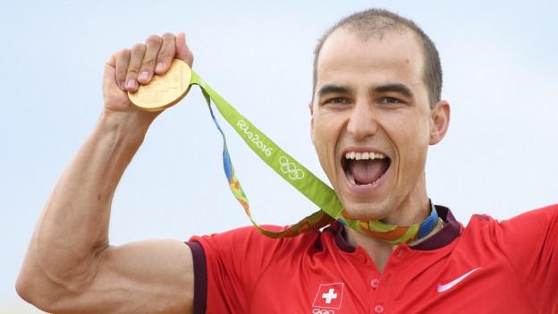 Mountainbiker Nino Schurter im roten Trikot, den Mund aufgerissen, die Goldmedaille um den Hals, er hält sie mit der rechten Hand in die Höhe.