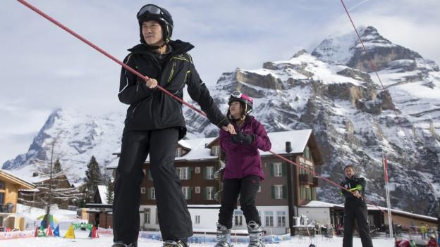 Chinesische Touristen in der Skischule im Berner Oberland.