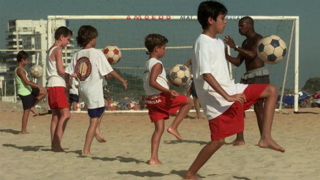 Ein paar Kinder spielen an einem Strand im Sand Fussball.