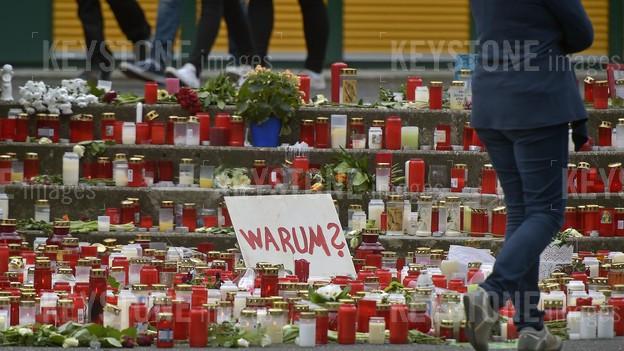 """Blumen und Kerzen auf einer Treppe, auf einem Schild steht in roter Schrift «Warum?""""."""