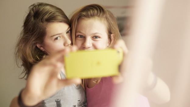 Zu sehen sind zwei Jugendliche, die mit einem Smartphone hantieren.