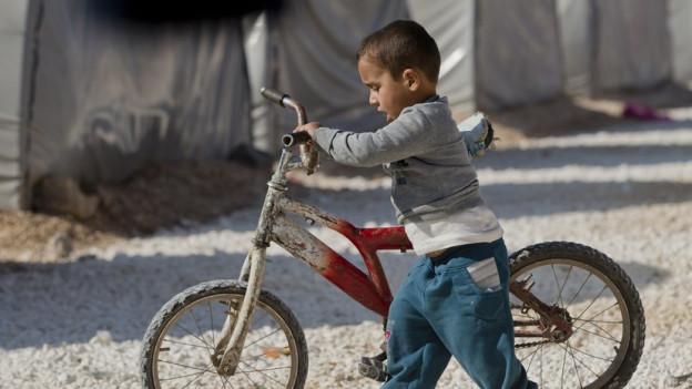 Ein Junge schiebt ein Fahrrad durch ein Flüchtlingslager.