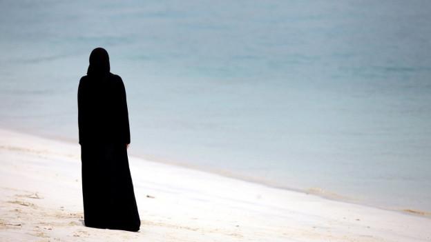 Eine verschleierte Frau spaziert am Strand.