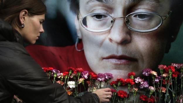 Ein Porträtfoto von Anna Politkowskaja, mit Brille und grauen Haaren, davor eine Frau, die Rosen niederlegt.