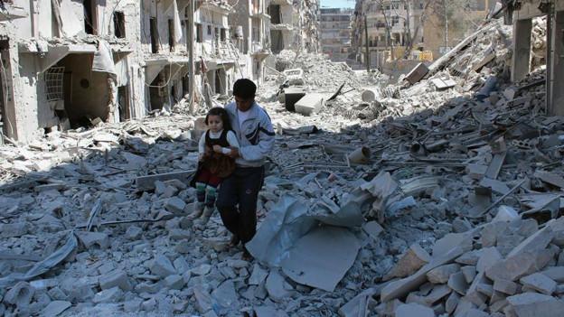 Ein Mann trägt ein kleines Mädchen über die Trümmer in der syrischen Stadt Aleppo.