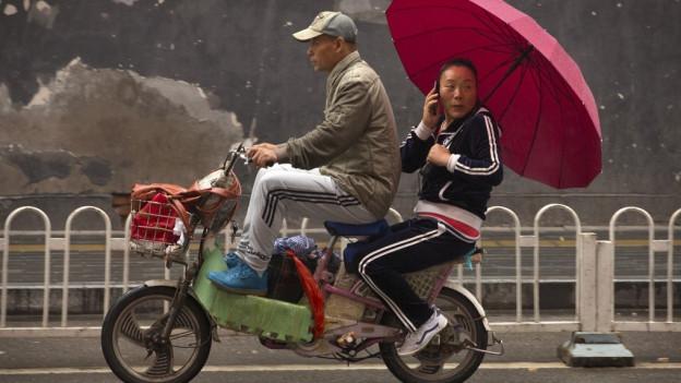 Eine Frau fährt mit Regenschirm Scooter.