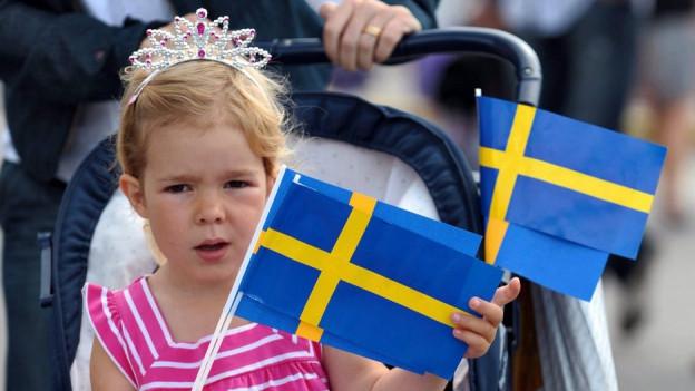 Ein Mädchen mit einer Schwedenfahne.