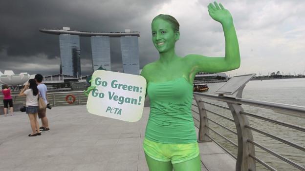 Eine Demonstrantin am Welt-Vegantag 2011 in Singapur, ganz grün angemalt, eine Tafel mit «Go green, go vegan» darauf, im Hintergrund die Marina Bay Sands (2. November 2011).