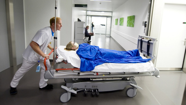 Ein Mann transportiert eine Kranke im Spital.