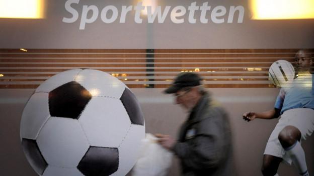 Ein älterer Herr geht an einem Schaufenster vorbei, darauf sind ein Fussballer und ein Ball zu sehen, darüber steht «Sportwetten».