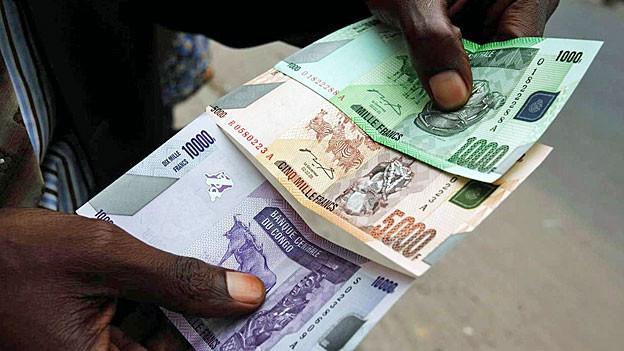 Die Hand eines Schwarzen, die ganz viele Geldscheine wie einen Fächer hält.