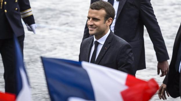 Frankreichs Präsident Macron lächelnd hinter einer französischen Flagge, hinter ihm zwei Körper in Anzug und Uniform.
