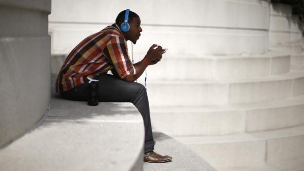 Ein Mann hört Radio auf seinen Kopfhörern.