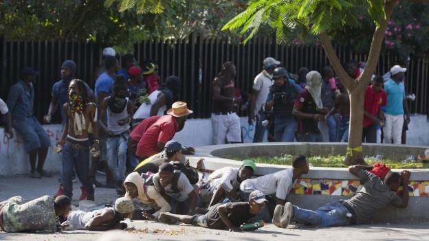 Demonstranten gehen in Port-au-Prince vor den Schüssen der Polizei in Deckung.