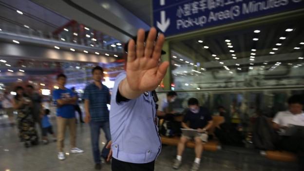 Hand vor Kamera an chinesischen Flughafen.