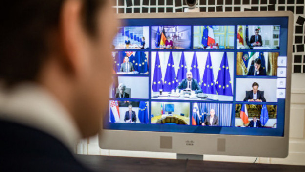Österreichs Bundeskanzler Sebastian Kurz sitzt vor einem Computerbildschirm auf dem andere EU Staats- und Regierungschefs zu sehen sind.
