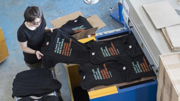 Medientechnologin steht in Druckerei neben T-Shirts mit Berset-Spruch.