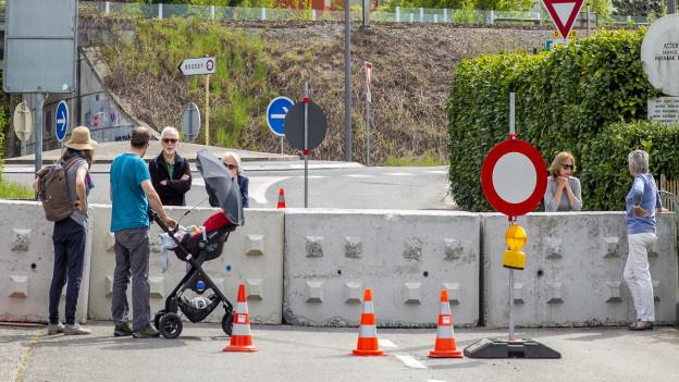 Personen unterhalten sich an der geschlossenen französisch-schweizerischen Grenze.